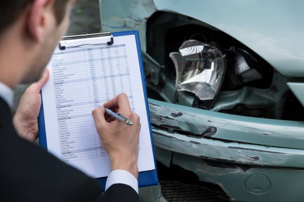 auto dañado con ajustador de seguros